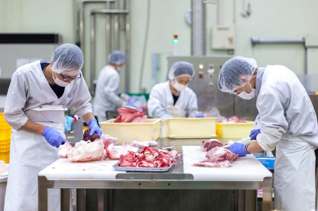 お肉を加工中の社員の画像